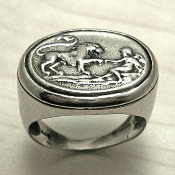 "A beautiful unisex signet ring that definitely tells a story. The intaglio on the top of the ring shows a Lion and a man ""Androcles"". This story tells about Androcles and the lion. Androcles, a runaway slave of a former Roman consul, takes shelter in a cave, which turns out to"