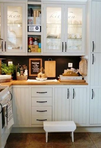 Tavlemaling på veggen mellom kjøkkenbenk og skap.