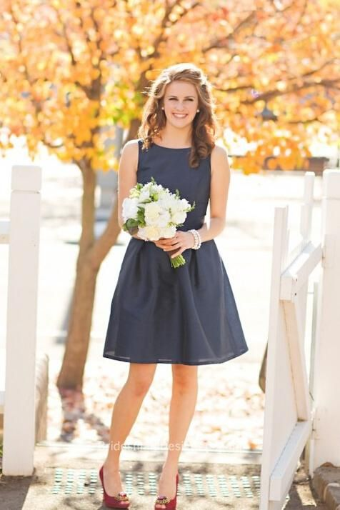 Short navy organza bridesmaid dress features sleeveless bodice with A-line sheer skirt, slight hand pleats adorned, beaded belt is attached at natural waist.
