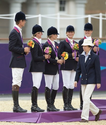Great Britain's Zara Phillips (third from left) on the podium with her fellow riders as her mother Princess Anne walks past after presenting the silver medals to the team July 31.