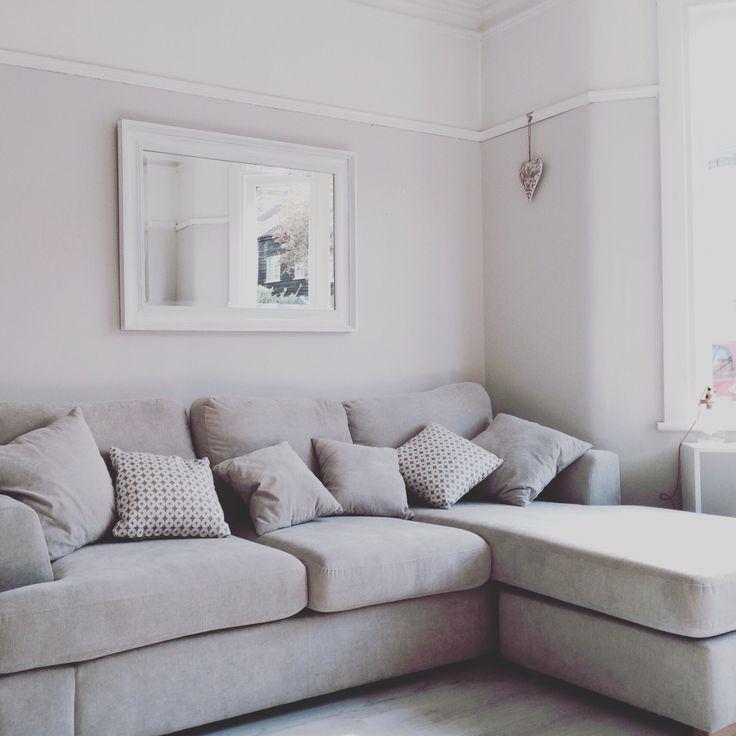 White walls , white floor boards, grey sofa
