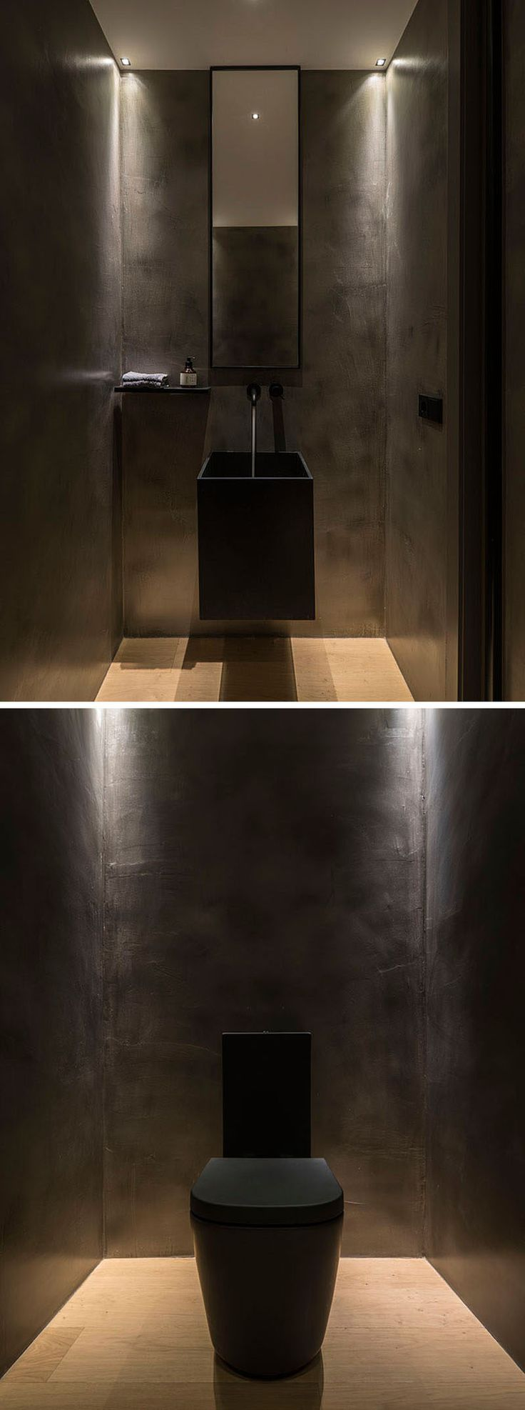 Inside this modern powder room, the walls, sink and toilet have been kept dark, creating a dramatic atmosphere,
