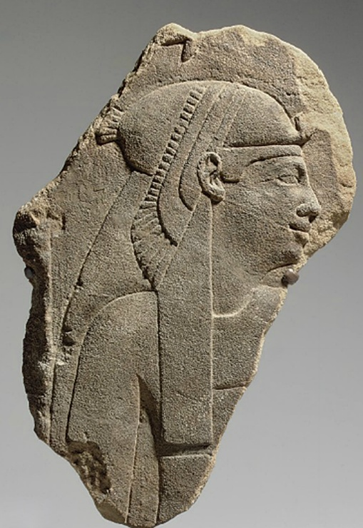 (Cone-heads?) AN EGYPTIAN SANDSTONE RELIEF PTOLEMAIC PERIOD, CIRCA 2ND CENTURY B.C. Sculpted in raised relief, preserving a queen or goddess, her face in profile to the right, her torso frontal, wearing a tightly-fitted sheath and a vulture headdress over a long tripartite wig, a lappet falling along the right side of her breast, her face with full lips, a prominent nose, and a protruding chin