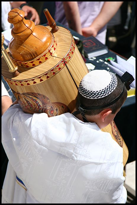 A boy carries the Torah roles back to the Western Wall, after reciting a part of it for his Bar Mitzva.