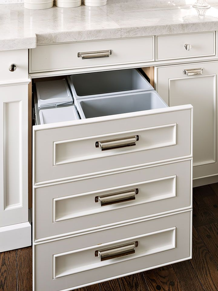 The recycling and garbage disposal are hidden behind a faux-finish panel of drawers with a large capactiy.