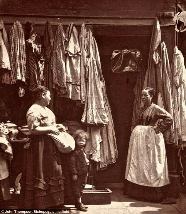 """An old clothes shop in St Giles London in the 1870's.  """"As a rule second hand clothes shops are far from distinguished in their cleanliness and are often the fruitful  medium  for  the propogation of fever and smallpox""""."""