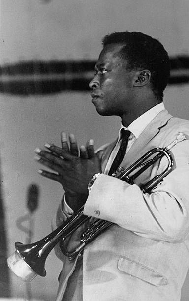 American jazz trumpeter and bandleader Miles Davis (1926-1991) looks to the side clapping while he holds his trumpet by his chest.