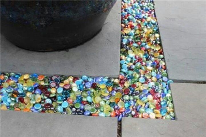 Twist on a concept: use glass pebbles instead of gravel to fill in spaces in the garden.