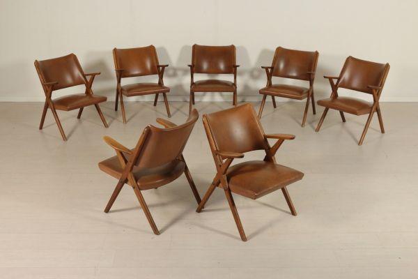 Gruppo di sette poltroncine anni 50; legno di faggio tinto, imbottitura in espanso, rivestimento in similpelle. Buone condizioni, presentano piccoli segni di usura.