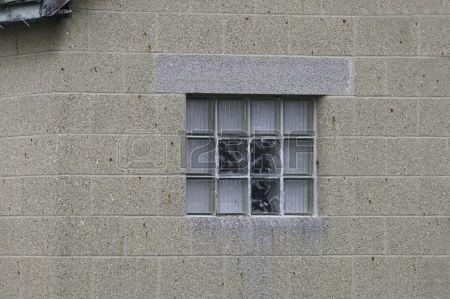 Una ventana de cristal del bloque en una pared de bloques de cemento  Foto de archivo