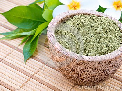 Henna powder in the coconut bowl, green leaves and tiare flowers