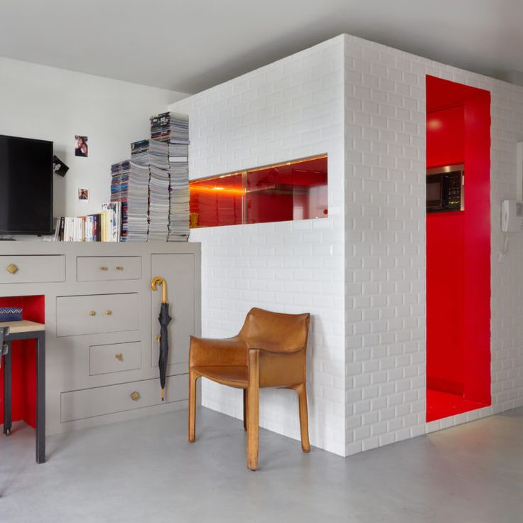 Côté salon, la flamboyance de la cuisine est rappelée par une niche qui pourrait faire penser à une cheminée. #deco #décoration #design #interior #inspiration #red #rouge #cuir #fauteuil #cuisine #kitchen #salon #livingroom #smallspace #carreaux #metropolitain #livres #bureau #desk #office