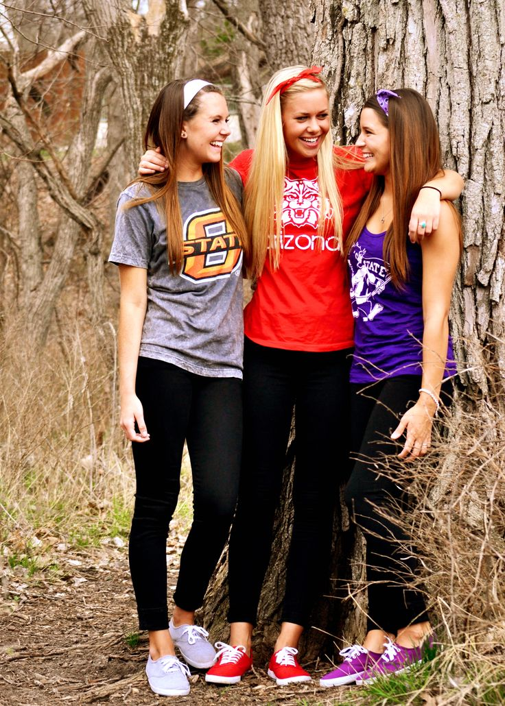 a senior picture with each friend wearing the shirt of the college they're going to
