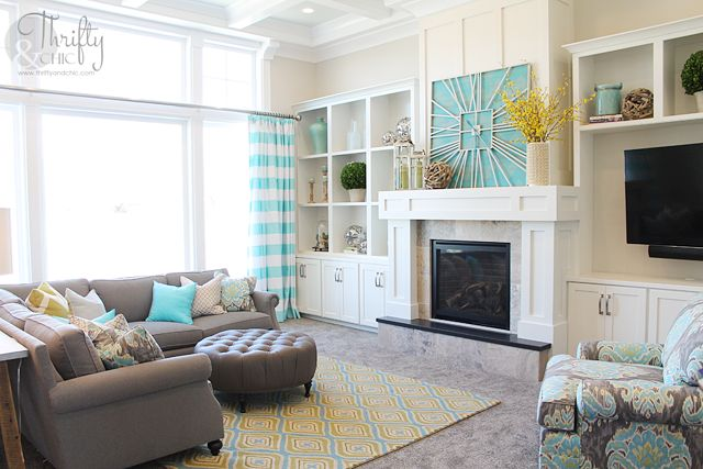 The gray base acts as the perfect neutral for the bright aqua and yellow colors in this well lit living room.