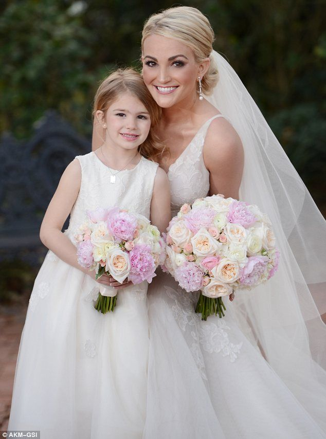 Her pride and joy: The five-year-old had a miniature version of her mother's wedding dress and they both carried bouquets of pastel coloured roses