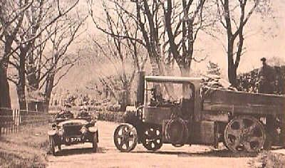 In 1916 a friction drive GWK moves to the 'wrong' side of this English road to pass a truck powered by an old steam engine. Notice exhaust steam.