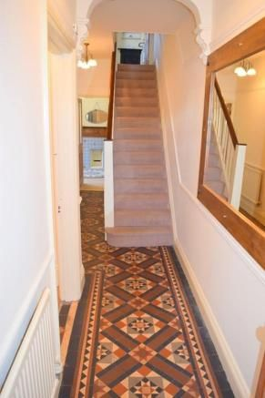 Classic Edwardian hallway with Minton (?) style tiles & decorative arch over the stairs