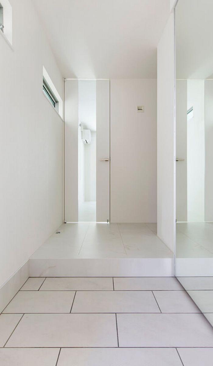 床から天井まで白で統一された 光が引き立つ明るい玄関ホール