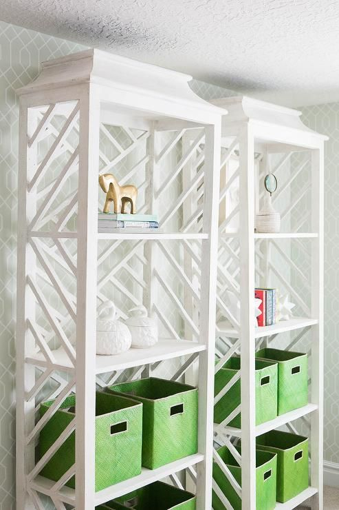 Chic living room boasts a pair of side by side white Fretwork bookcases, Meiling Bookcase White Weathered, lined with emerald green woven bins, Serena & Lily Pandan Bins.