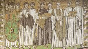 """Basilica di San Vitale; ca 546-548 d.C.; Ravenna. Mosaico del presbiterio, """"Giustiniano e il suo seguito"""".  L'imperatore e l'imperatrice (qui non visibile) portano all'altare le offerte del pane e del vino il giorno della consacrazione della basilica. Giustiniano, centrale, e rivestito da un manto di porpora, ha alla sua destra consiglieri e soldati, mentre alla sua sinistra i rappresentanti del clero e il vescovo Massiminiano."""
