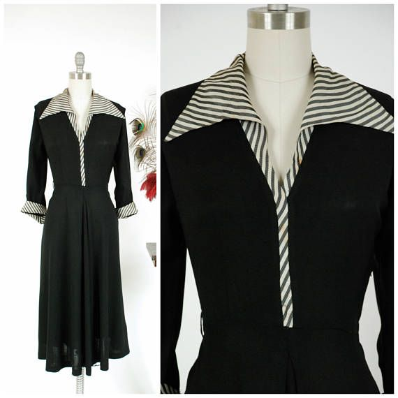 Vintage 1940s day dress in a classic black rayon crepe. A dramatically pointed collar and matching turned cuffs are made of a striped acetate with subtle plaid effect - white, pewter grey and a ghostly silver. The post-war silhouette features a flared skirt with deep front vent, and crisply tailored bodice, with shoulder vents. The three quarter sleeves are a perfect length - its the sort of dress you can wear to work, to shop or to go out on a Saturday. Smart, timeless. This dress closes…