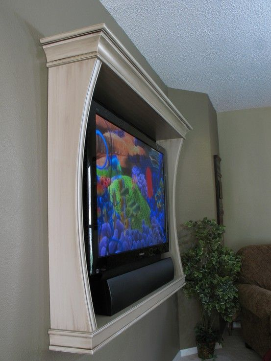 This is a simple yet elegant tv surround with flat sides, molded edges, and decorative molded top and bottom.  The bottom piece of this unit serves as a shelf to hold the speaker bar under the tv.  There is no tutorial linked to this image but I wanted to share it as inspiration.  Looks really impressive yet can be so easy to design and build.