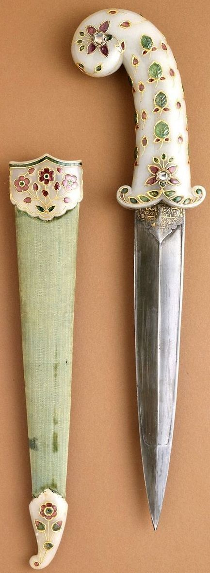 Indian (Mughal) dagger, circa 1675-1700 (sheath fittings, circa 1800),  white nephrite jade hilt and sheath fittings inlaid with foiled rubies, emeralds, and diamonds set in gold; steel blade; velvet covered wooden sheath Measurements: 16 7/8 x 3 x 1 in. (42.86 x 7.62 x 2.54 cm), LACMA.