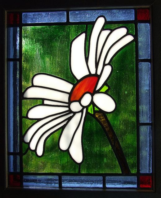 Daisy, my third attempt at stained glass work.  This daisy was one of thousands in a border at Great Dixter during a college visit in May 2006. Picking the right one to make was the 'fun' part. My challenge in this piece was the large areas of green glass where I wanted less joins to balance the picture.  My other examples can be found on A Pain in the Glass