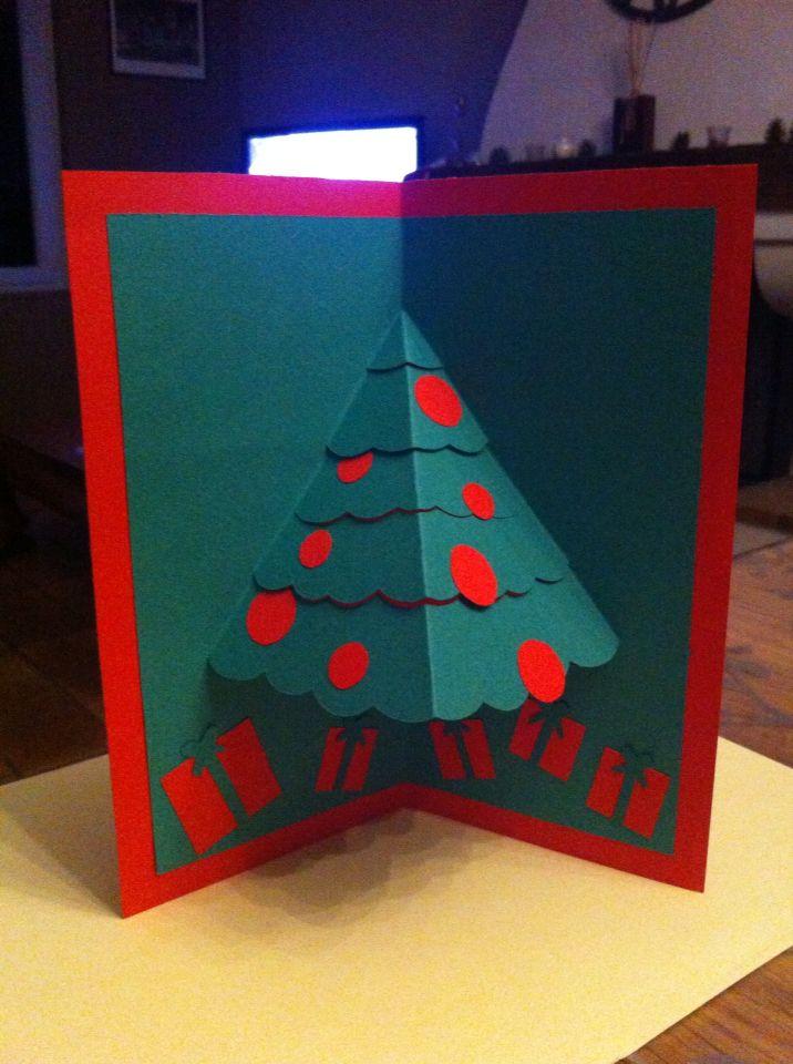 Carte de Noël fait main, pour cela prendre 2 feuilles type canson de couleurs différentes ici rouge et verte, la feuille de l intérieur sera moins grande, la plier en 2 dessiner la moitié d un sapin, découper et pousser les parties découpées vers l arrière, coller ensuite les 2 feuilles l une sur l autre et y rajouter de la deco, ici on a rajouté des boules et des cadeaux!