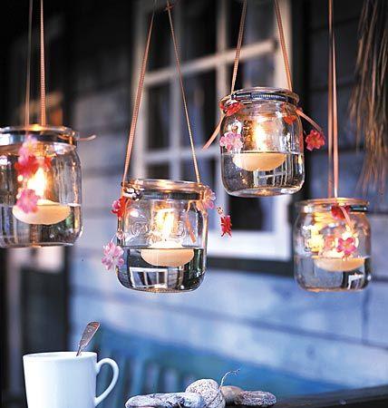 Stimmungsvolle Stunden  Dazu Windlichter mit Schlauchschellen (Baumarkt) versehen, mit Bändern befestigen und mit Stoffblumengirlanden verzieren, dann mit Wasser und Schwimmkerzen füllen.