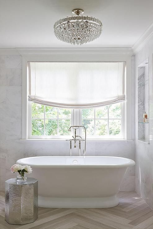 Sophisticated, elegant bathroom features a crystal semi flush mount hanging over an oval freestanding tub and floor mount tub filler placed under windows dressed in one white roman shade and a marble niche lined with glass shelves alongside a hammered metal accent table atop a herringbone floor.