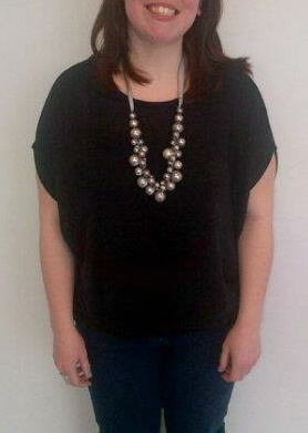 Meet Ashley, she is today's Feature Friday! She is wearing a gorgeous black dolman sweater paired with dark wash skinny jeans. This girl knows how to accessorize! She is wearing a gorgeous pearl necklace with a ribbon tie, and not shown in the photo is a great statement ring with contrasting lavender nail polish.
