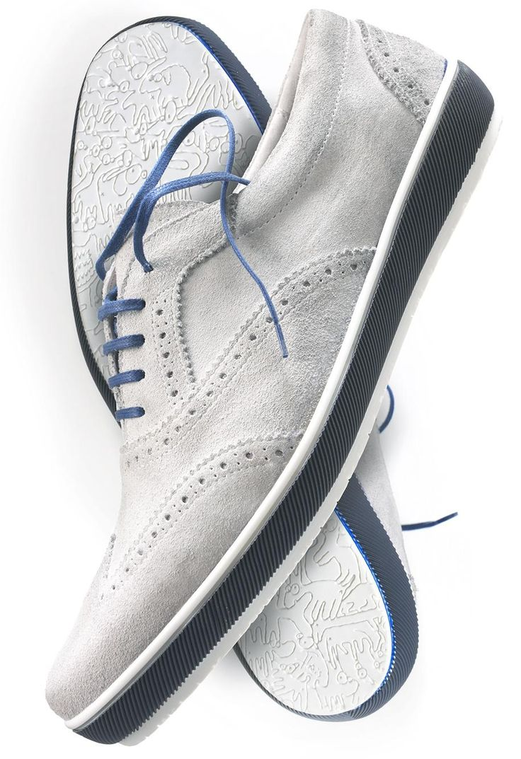 White wingtip sneakers with contrasting base and shoe laces.