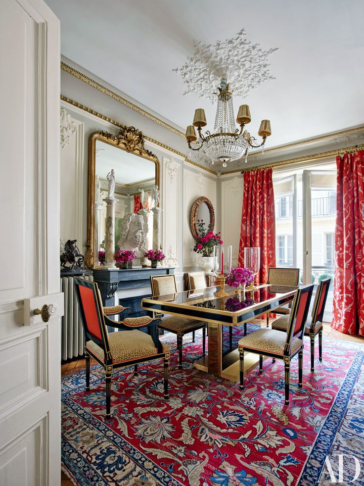 Curtains of a Timothy Corrigan Collection fabric for Schumacher make a brilliant splash in the dining room of the designer's Paris apartment.