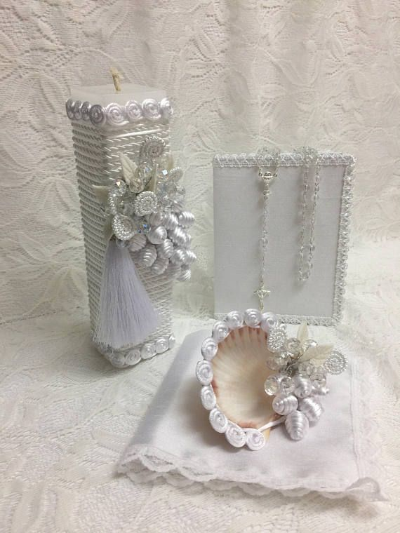 Baptism ceremony candle set white color candle decor with Crystals and pearls, and hand made porcelain flowers ribbons fabric flowers made with ribbons and made with dedication and love. This set included 1 candle 1 rosary 1 mini book with prayers (this tiny book only I have in Spanish