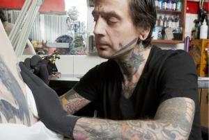 Tattoo artist doing a tattoo - Nicola Tree/Taxi/Getty Images