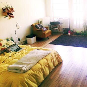 リビングとベッドルームを兼ねたワンルームには、ロータイプのベッドがおすすめです。黄色の明るいファブリックが、空間の棲み分けに一役かっていますね。