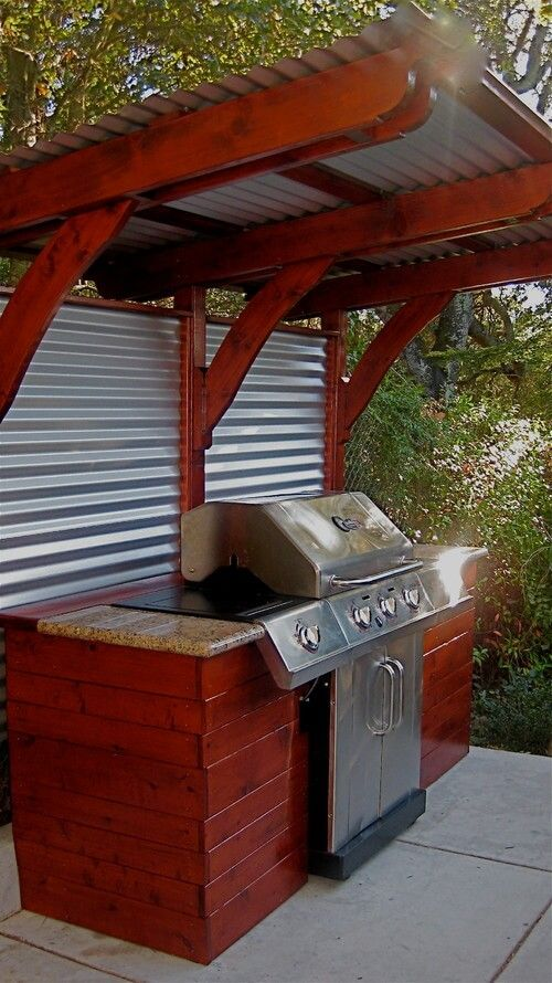 The backside of this wooden grill gazebo is fitted with aluminum siding to keep the foliage from growing into the cooking area.