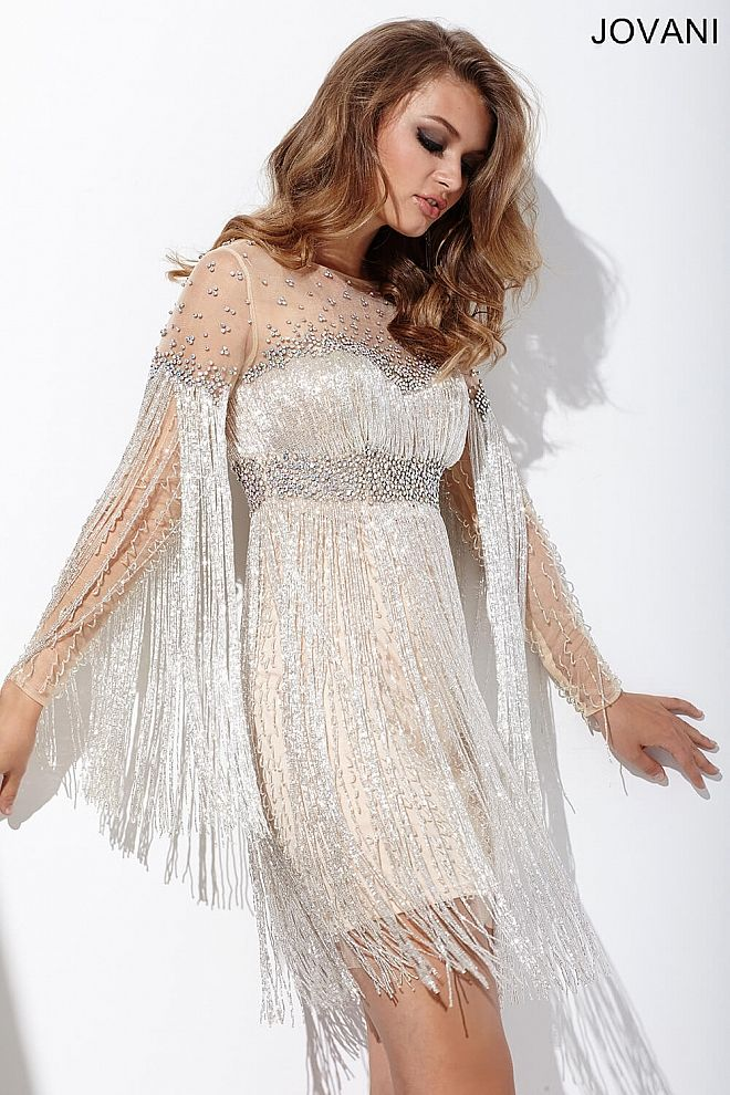 Fitted nude short cocktail dress features long sleeves, fringe detailing, crystal embellishments a sheer back and a zipper in the back.