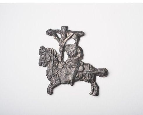Święta Krew. Plakietka przedstawiająca rycerza na koniu z ogonem splecionym w węzeł. Jeździec trzyma lewą ręką uzdę, a w prawej ma oparty o łęk siodła duży krzyż z przybitym Chrystusem. Fot. Joanna Szmit, Creative Commons