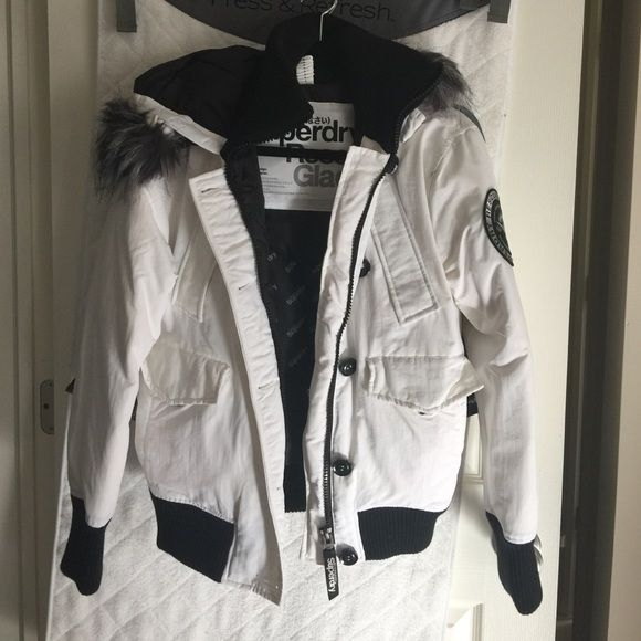 Brand new!!   Superdry jacket White Superdry Jacket.  Never worn.  Brand new.   Black zipper and button detail.  Fur trimmed hood. Superdry Jackets & Coats