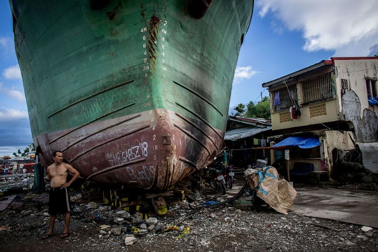 A man stands in front of a large ship grounded by Typhoon Haiyan on April 18, 2014 in the Philippines. CHRIS MCGRATH/GETTY IMAGES