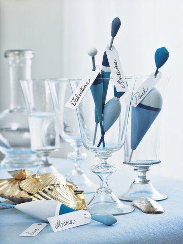 Des marque-place comme des flotteurs de pêche peints et ornés d'une étiquette pour le mariage marin