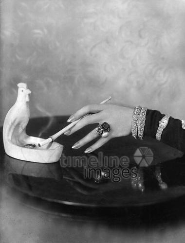 Hand hält eine Zigarette mit Zigarettenspitze ullstein bild - Ernst Sandau/Timeline Images #Zigarette #cigarette #rauchen #smoking #Frau #black #white #photography #schwarz #weiß #Fotografie #historisch #historical #traditional #traditionell #retro #nostalgic #Nostalgie #Aschenbecher #Zigarettenhalter #Schmuck #Handmodel #20er #20s #Hand #Ring