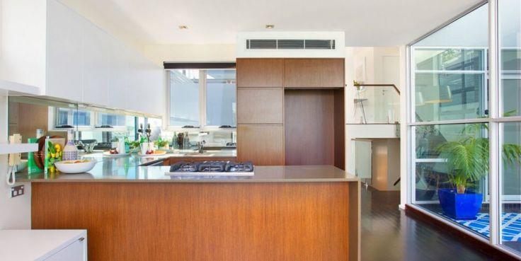 mirrored splashback, stone benches, timber cabinetry, dark timber flooring
