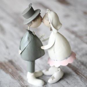 Figura novios beso  Parejita de novios para el pastel de bodas o como decoración. La pareja se da un divertido beso gracias a un imán que hace que sus labios permanezcan unidos. En http://www.unabodaoriginal.es