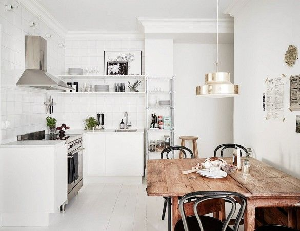 Modern Swedish kitchen with a wooden dining table and exposed shelves.
