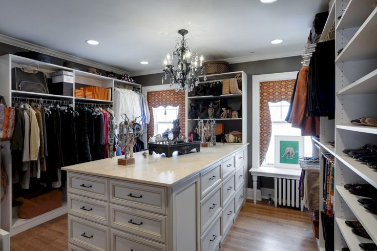"""The center of this custom closet has a large marble-topped """"island"""" with drawers for jewelry storage, among other things. Two windows flank the island, and a small, elegant chandelier hangs above it."""