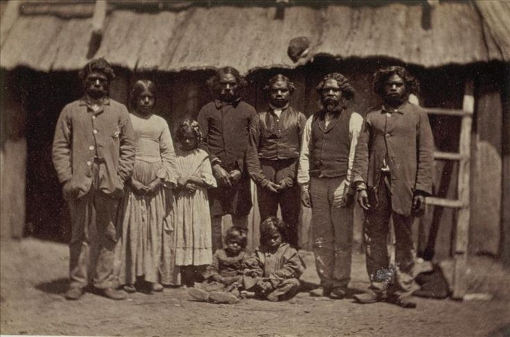 Group of Aboriginal men, women and children, standing in front of slab hut ca. 1857-1859. This image was taken by Antoine Fauchery and Richard Daintree between late 1857 and early 1859 for inclusion in their Photographic Series Sun Pictures of Victoria.