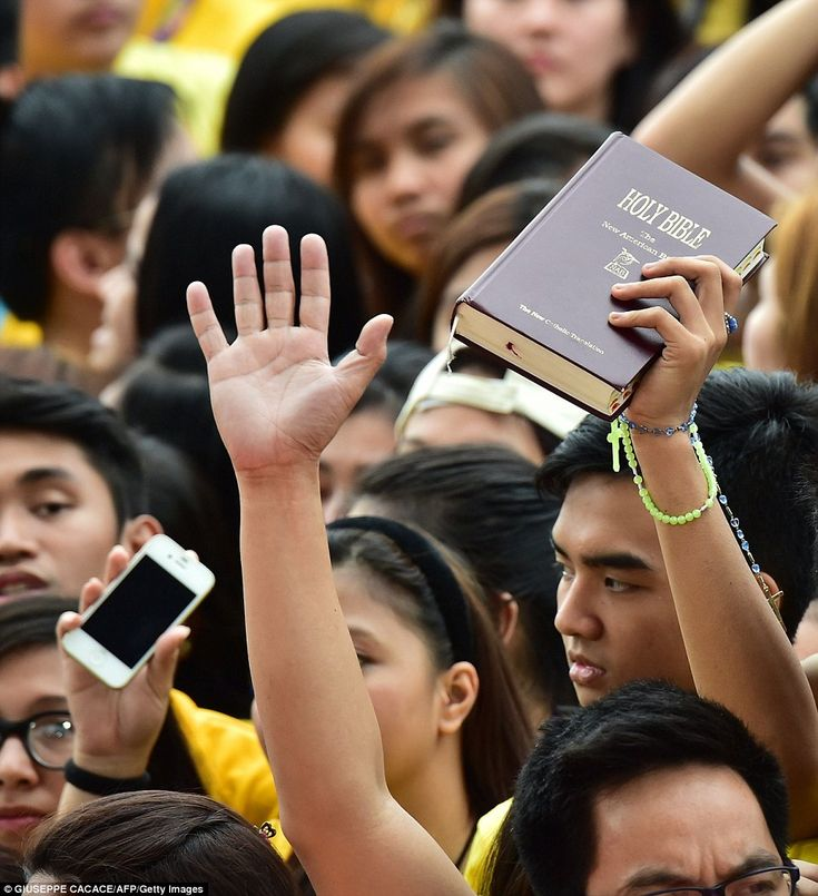 Pious: A student holds a Bible during the visit by Pope Francis to the University of Santo Tomas in the Philippines.